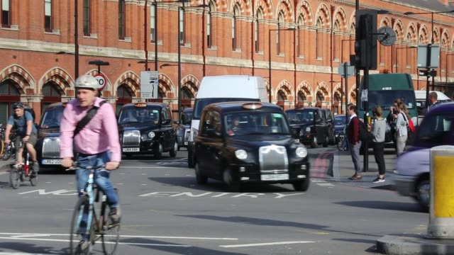 cyclists and taxi's wait to cross a junction by st pancras railway station, euston road, london, uk. - brick stock videos & royalty-free footage