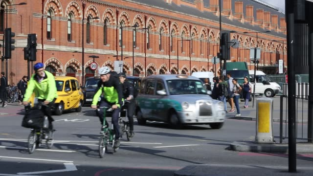 cyclists and taxi's wait to cross a junction by st pancras railway station, euston road, london, uk. - road junction stock videos & royalty-free footage