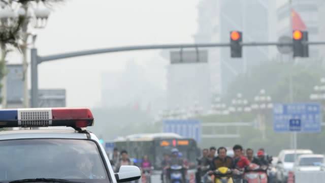 cyclists , cars and police car patroling in beijing, china - smog stock videos & royalty-free footage
