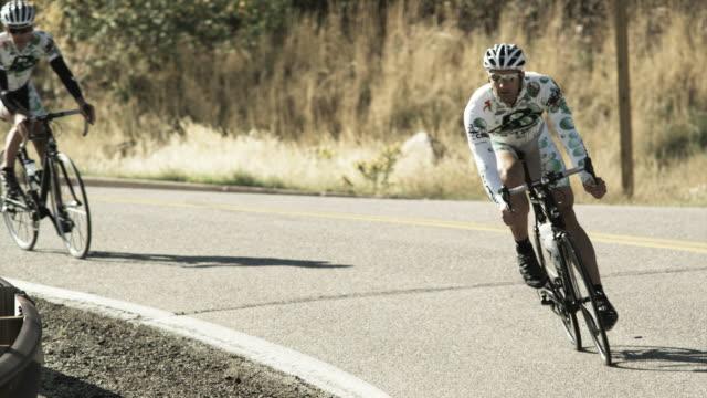 cyclists coming downhill around a bend - 曲線点の映像素材/bロール