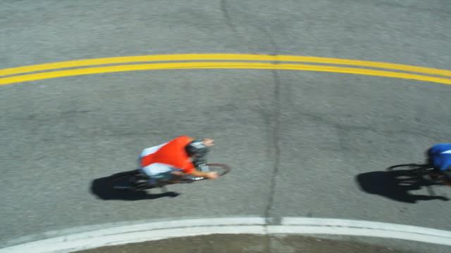 vídeos de stock e filmes b-roll de cyclists coming downhill around a bend - bicicleta de corrida