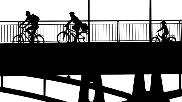 b/w cyclists crossing a bridge - überqueren stock videos and b-roll footage