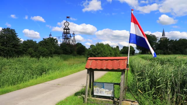 """cyclists go by as the dutch flag waves in the wind near the steel replica of the """"uniastate"""" designed by artist bep mulder on july 12, 2020 in bears,... - illusion stock videos & royalty-free footage"""