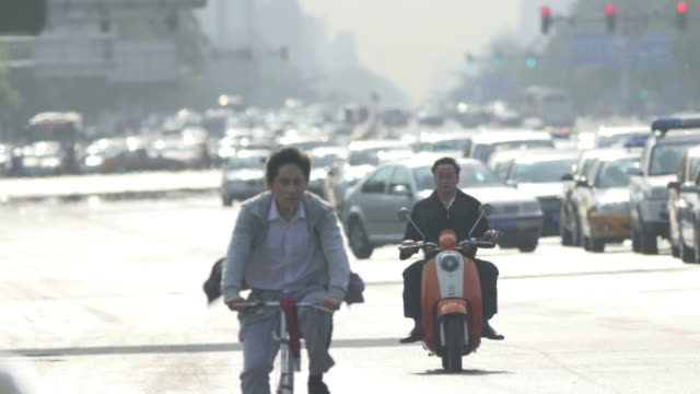 cyclists in rush hour traffic in beijing, china - peking stock-videos und b-roll-filmmaterial