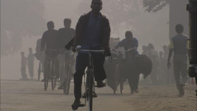cyclists negotiate heavy traffic under a hazy sky. - population explosion video stock e b–roll
