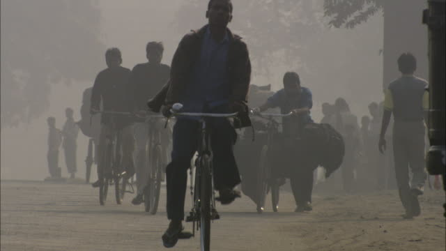 cyclists negotiate heavy traffic under a hazy sky. - india video stock e b–roll