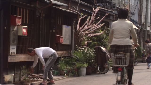vídeos de stock e filmes b-roll de cyclists pass by as people tend to plants outside their houses in shitamachi area - bairro antigo