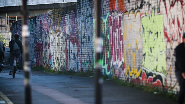 cyclists pass graffiti wall in deptford, london - focus on background stock videos & royalty-free footage