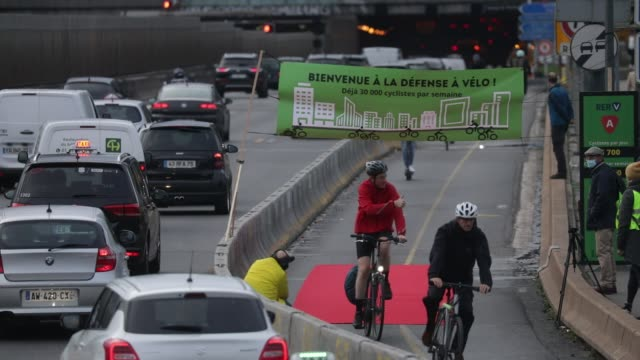 "cyclists pass on a red carpet, above their heads a banner with the message ""welcome to la defense a velo, already more than 30,000 cyclists per week""... - île de france stock-videos und b-roll-filmmaterial"