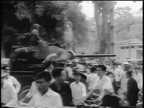 b/w 1963 cyclists passing tank on street / celebration of new government / south vietnam / newsreel - south vietnam stock videos and b-roll footage
