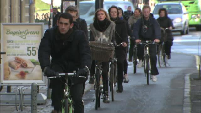 Cyclists pedal down a narrow street in Copenhagen.