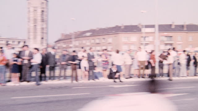 1974 montage cyclists racing on bicycles on city streets as spectators are watching the race / united kingdom - 1974 bildbanksvideor och videomaterial från bakom kulisserna