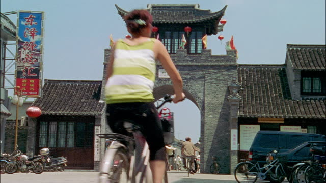 cyclists ride through an arched gate on a city street in zhejiang, china - zhejiang province stock videos & royalty-free footage