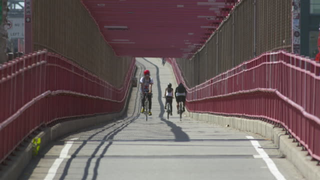 Cyclists ride up and down the Williamsburg Bridge bike path.