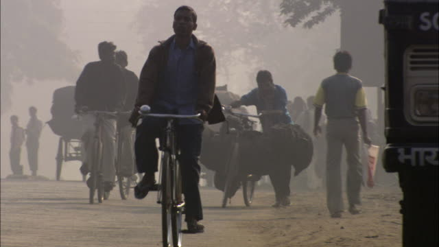 ws ms cyclists riding bikes down busy street under hazy sky / india - smog video stock e b–roll