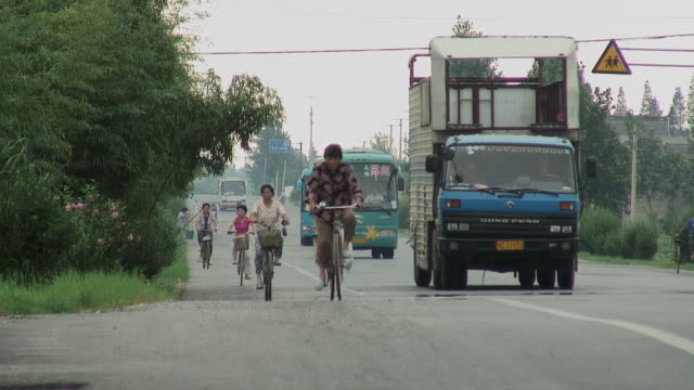 WS Cyclists riding on roadside as trucks and buses pass by/ Subei, China