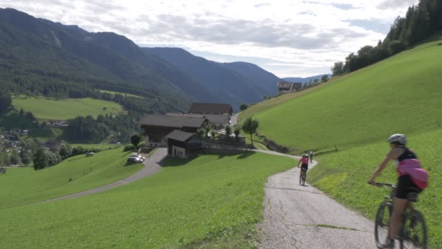 cyclists riding through val di funes, bolzano province, trentino-alto adige/south tyrol, italian dolomites, italy, europe - italian culture stock videos & royalty-free footage