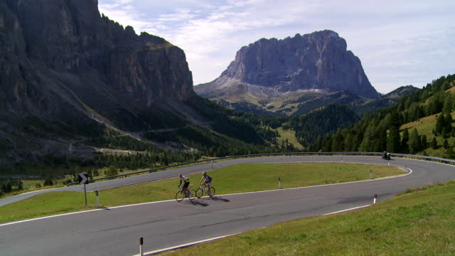 ha cyclists riding up gardena pass (passo gardena) in the dolomites mountains - langkofel stock videos & royalty-free footage