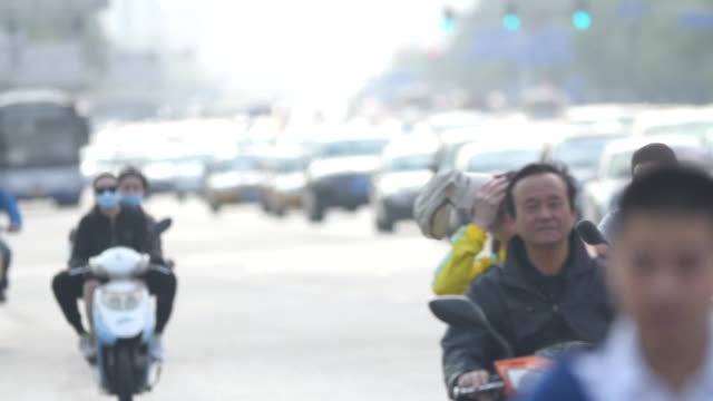 Cyclists wearing mask in rush hour traffic in Beijing, China