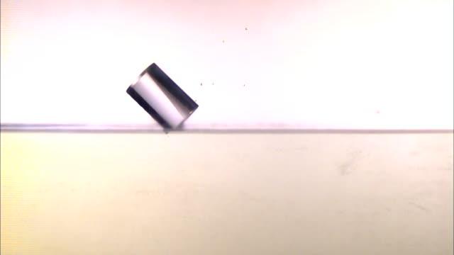 vídeos de stock, filmes e b-roll de a cylinder falls at an angle into a layer of water and splashes. - tensão de superfície
