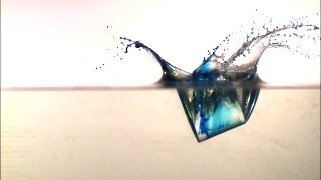 vídeos de stock, filmes e b-roll de a cylinder falls into a layer of water and splashes. - tensão de superfície