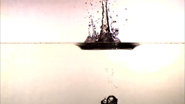 vídeos de stock, filmes e b-roll de a cylinder falls into a tank of water and splashes. - tensão de superfície