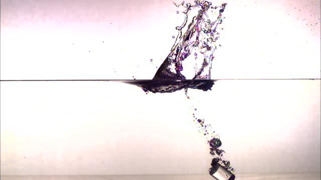 vídeos de stock, filmes e b-roll de a cylinder falls into a tank of water at an angle and splashes. - tensão de superfície