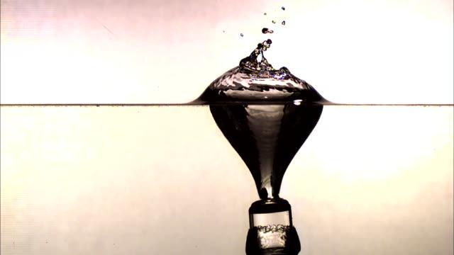 vídeos de stock, filmes e b-roll de a cylinder falls straight down into a layer of water and splashes. - tensão de superfície