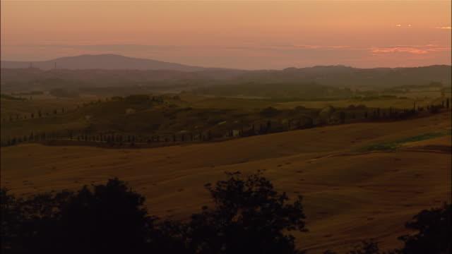 cypress trees flank harvested fields in crete, senesi, siena, tuscany, italy. - toskana stock-videos und b-roll-filmmaterial