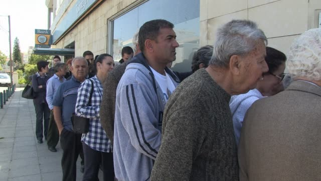 cyprus banks reopened under armed guard thursday after a nearly two week lockdown but customers faced harsh curbs to stop them draining the islands... - financial accessory stock videos & royalty-free footage