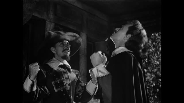 Cyrano De Bergerac (José Ferrer) helps a man (William Prince) articulate his feelings for woman (Mala Powers)