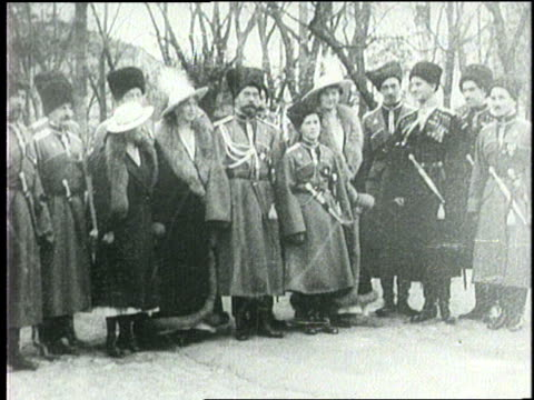 Czar Nicholas II and his family stand outdoors together in full winter dress