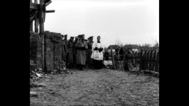 Czar Nicholas II and the Archbishop of Poland walk in the ruins of a village destroyed during military fighting
