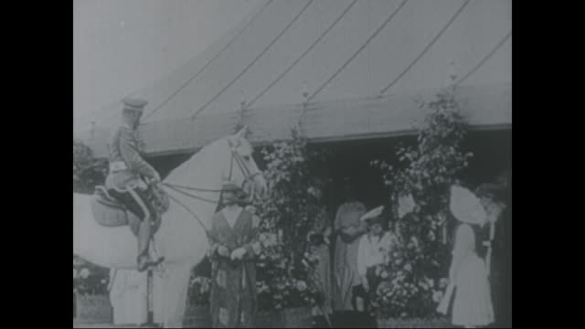 Czar Nicholas II of Russia rides his horse and meets people stands with his daughters