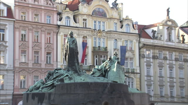 a czech republic flag waves behind a statue of jan hus in prague's old town square. - prague old town square stock videos & royalty-free footage