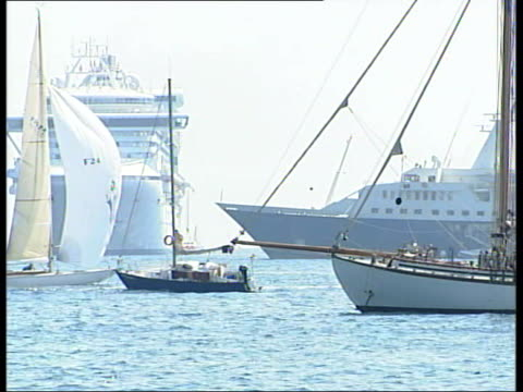 world premiere at cannes film festival; france: cannes: ext ferries and yachts offshore at resort large man sunbathing on beach back view woman... - the da vinci code stock videos & royalty-free footage