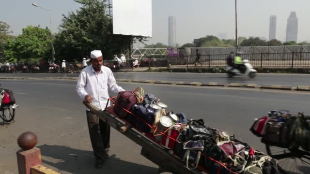 Dabbawallas delivering packages from suppliers to destinations in Mumbai India on December 12 2015 Shots CU of man's face as he waits on train CU of...