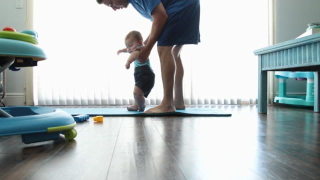 Dad and baby son (7-9months) exercising at home