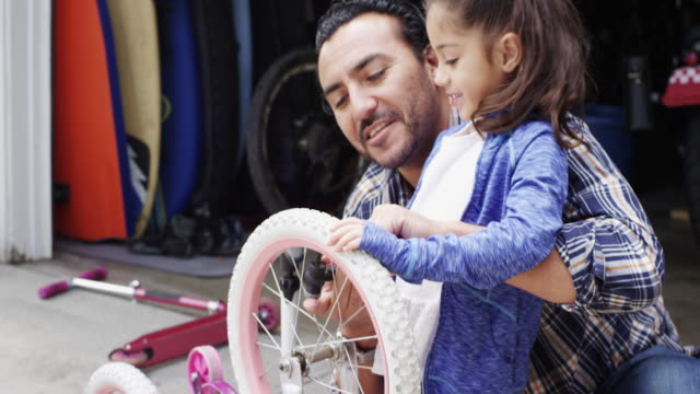 Dad and daughter fixing bicycle, putting air in the tires.
