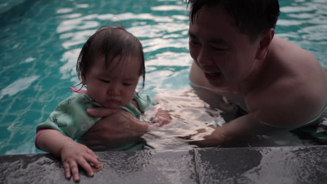 Dad and girl swimming in the pool