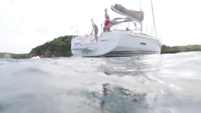 dad and kids jumping off boat - swimwear stock videos & royalty-free footage