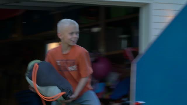 stockvideo's en b-roll-footage met dad and kids load bags into mini camper, cu - familie met drie kinderen