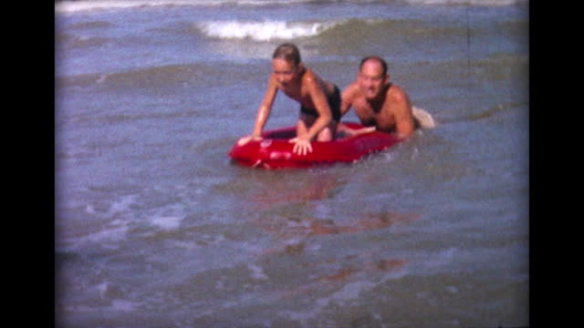 1964 dad and kids on raft in the surf - di archivio video stock e b–roll