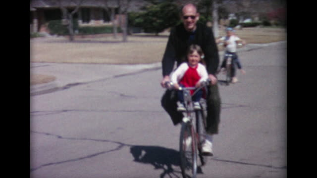 1965 dad and kids ride bikes in suberbs - nachbar stock-videos und b-roll-filmmaterial