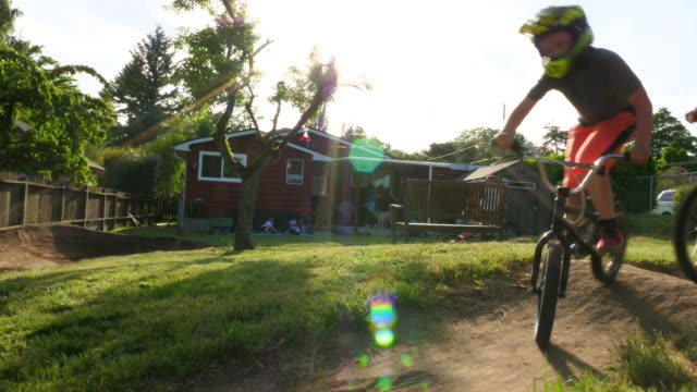 pan dad and kids riding bmx bikes around a backyard pumptrack on summer evening - bmx stock-videos und b-roll-filmmaterial