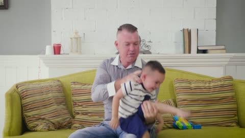 stockvideo's en b-roll-footage met papa en zoontje plezier spelen op sofa in de woonkamer bij u thuis - genderblend