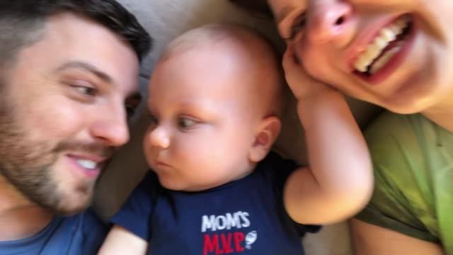 vidéos et rushes de papa et maman s'amusant sur le lit avec leur fils pris d'un appareil mobile - filmer