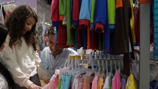 dad and mom listening to their daughter while she is talking and pointing at a shirt she likes at a clothing store - second hand stock videos & royalty-free footage