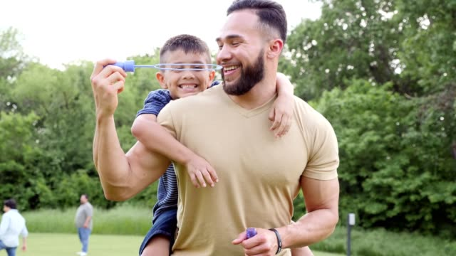 dad and son blowing bubbles in the park - bubble wand stock videos & royalty-free footage