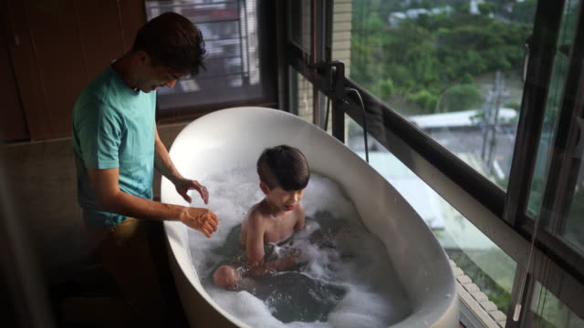 vídeos y material grabado en eventos de stock de papá e hijo divirtiéndose durante el baño - domestic bathroom